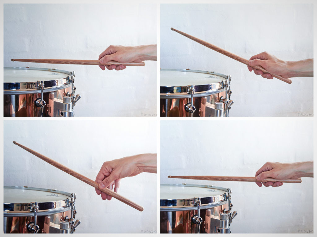 Hand holding stick demonstrating grip and stroke on snare drum
